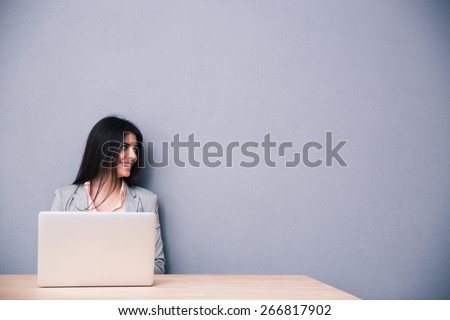 Portrait of a happy woman sitting at the table with laptop and looking away over gray background - stock photo