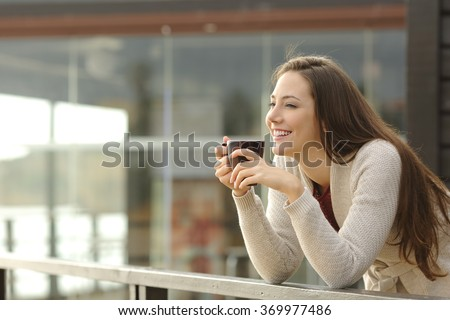 Portrait of a happy woman thinking and looking away at breakfast on vacation with a resort or hotel on the beach in the background - stock photo