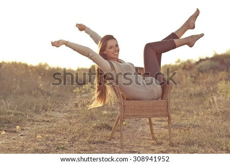 Portrait of a happy woman, warm autumn sunset - stock photo