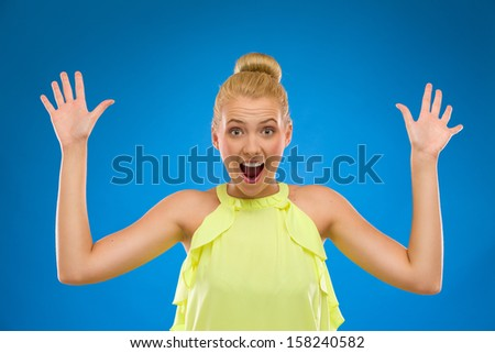 Portrait of a happy woman with hands up. Studio shot isolated on blue. - stock photo