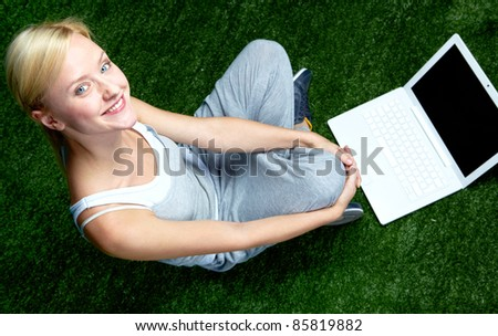 Portrait of a happy woman with laptop looking at camera and smiling - stock photo