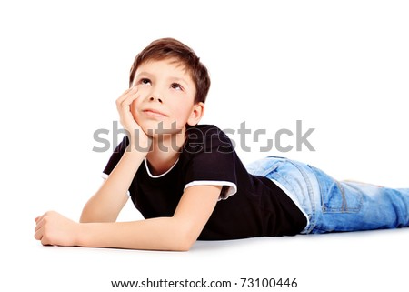 Portrait of a happy 9 year boy lying on a floor. Isolated over white background. - stock photo