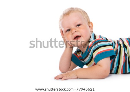 Portrait of a happy 2 year boy lying on a floor. Isolated over white background.