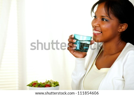 Portrait of a happy young adult woman with a sincere smile and drinking fresh water while looking to her right. With copyspace. - stock photo