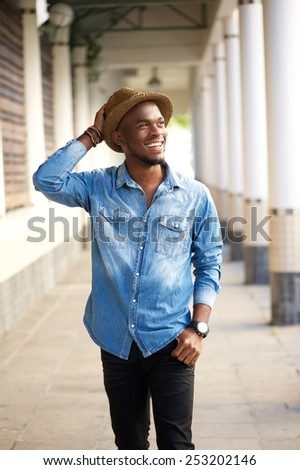 Portrait of a happy young african american man walking with hat - stock photo