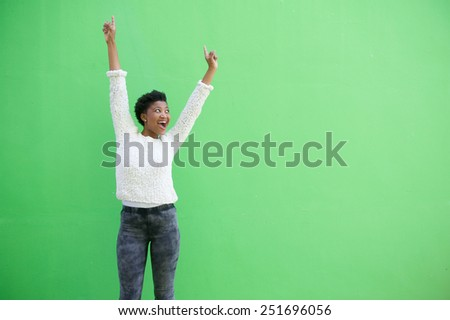 Portrait of a happy young african american woman cheering with arms raised - stock photo
