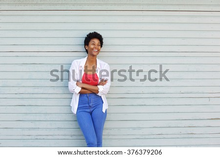 Portrait of a happy young african woman with arms crossed standing against a wall and looking away - stock photo