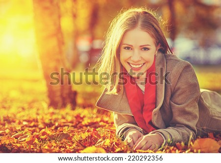 portrait of a happy young beautiful woman on an autumn walk - stock photo