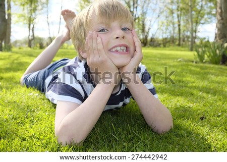 Portrait of a happy young boy in the garden - stock photo