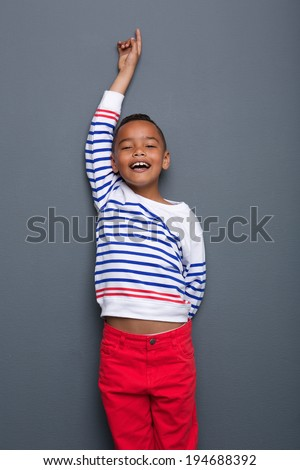 Portrait of a happy young boy with arm raised and finger pointing up on gray background - stock photo