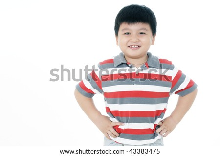 Portrait of a happy young boy with hands on his hips on white background. - stock photo