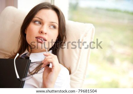 Portrait of a happy young brunette woman holding book sitting on comfortable chair near window with natural light. Wearing eyeglasses - stock photo