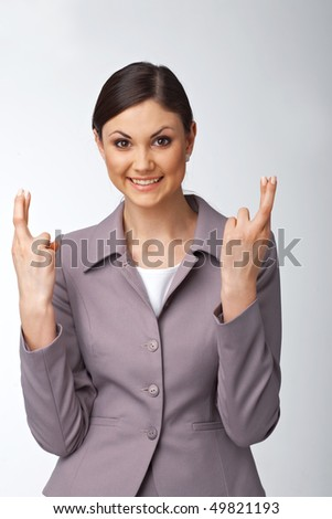 Portrait of a happy young business woman with fingers crossed - stock photo