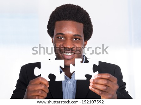 Portrait Of A Happy Young Businessman Holding Jigsaw Puzzle - stock photo