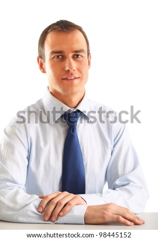 Portrait of a happy young businessman sitting on the desk - stock photo