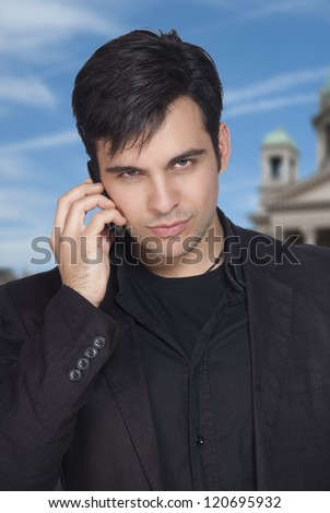 Portrait of a happy young businessman talking on cellphone.