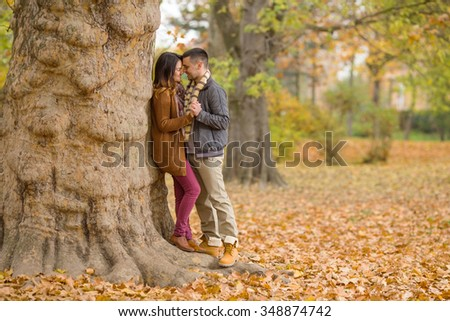 Portrait of a happy young couple enjoying their love in nature on a nice autumn day - stock photo