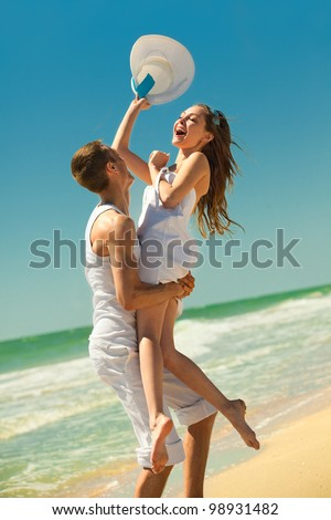 Portrait of a happy young couple having fun on the beach. Young man lifting his woman on beach.Couple enjoying a summer vacation.