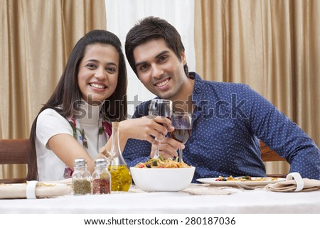 Portrait of a happy young couple having wine at restaurant - stock photo