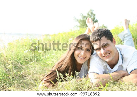 Portrait of a happy young couple lying on grass in a park - Outdoor - stock photo