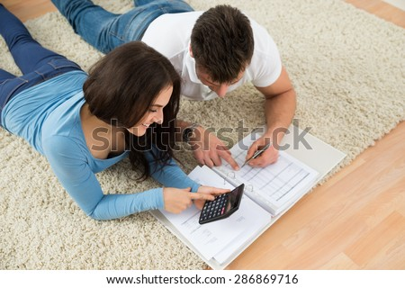 Portrait Of A Happy Young Couple Lying On Rug Calculating Invoice - stock photo