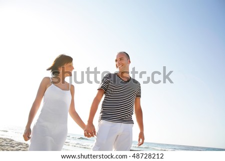 Portrait of a happy young couple taking a walk on the beach.