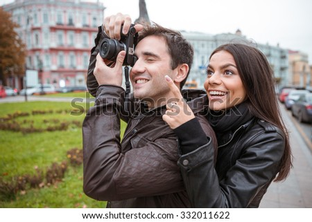 Portrait of a happy young couple traveling and making photo on camera in old european city