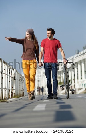 Portrait of a happy young couple walking outdoors pointing - stock photo