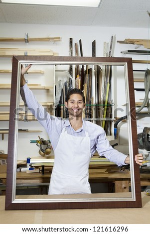 Portrait of a happy young craftsman holding big frame in workshop - stock photo