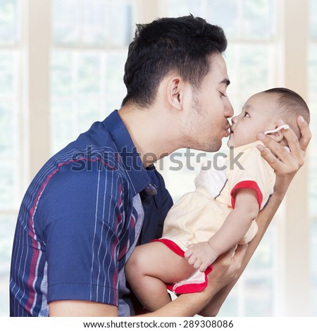 Portrait of a happy young dad lifts and kiss his baby boy at home - stock photo