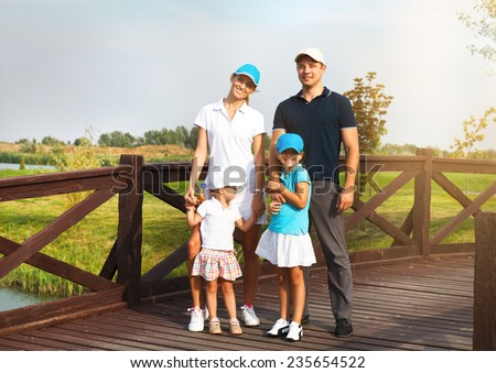 Portrait of a happy young family in golf country club - stock photo