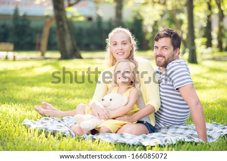 Portrait of a happy young family spending their free time in the park - stock photo