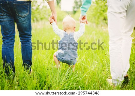 Portrait of a happy young family teaching baby to walk in the park - stock photo