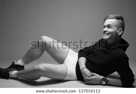 Portrait of a happy young fashionable man in trendy clothes sitting over gray background. Perfect haircut. Hipster style. Copy-space. Black and white (monochrome) studio shot - stock photo