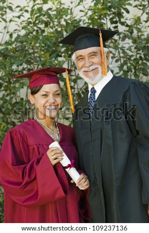Portrait of a happy young female graduate holding certificate with dean - stock photo