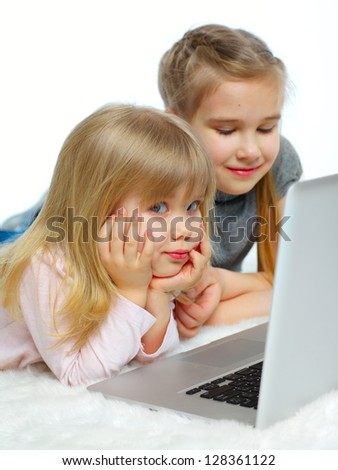 Portrait of a happy young girls with laptop computer. Vertical view. Isolated over white background - stock photo