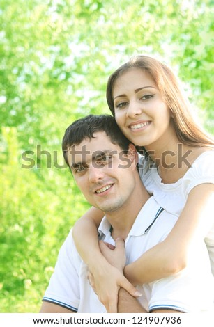 Portrait of a happy young hispanic couple sitting on green grass in a spring park - Outdoor - Space for inscription