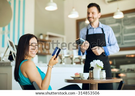 Portrait of a happy young Hispanic woman showing her credit card after using it at a coffee shop - stock photo