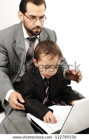 Portrait of a happy young man and his son working on laptop - stock photo