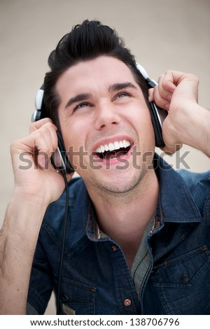 Portrait of a happy young man listening to music on earphones outdoors - stock photo