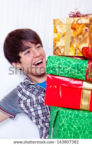 Portrait of a happy young man looking at gifts pile - stock photo
