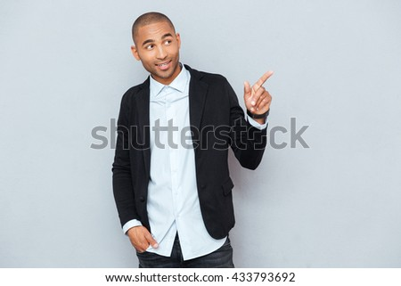 Portrait of a happy young man pointing at something interesting isolated on gray background - stock photo