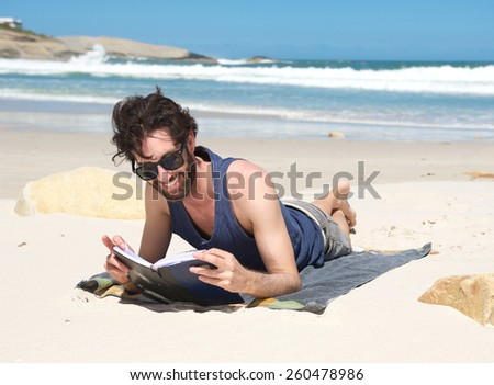 Portrait of a happy young man reading book at the beach