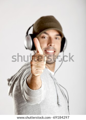 Portrait of a happy young man showing thumbs up and listen music with headphones