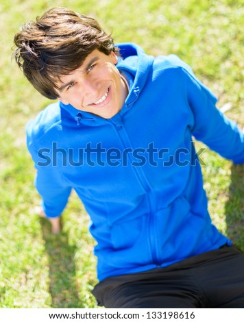 Portrait Of A Happy Young Man Sitting In Park - stock photo
