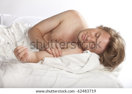 Portrait of a happy young man sleeping and smiling in his bed. Studio shot. See more in my portfolio - stock photo