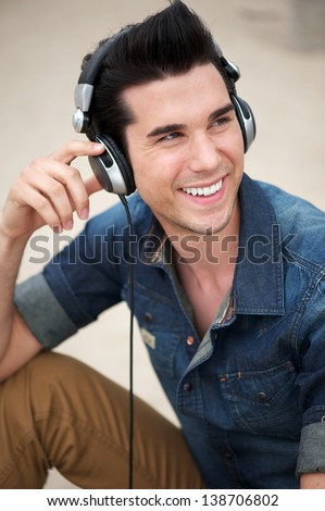 Portrait of a happy young man smiling with headphones - stock photo
