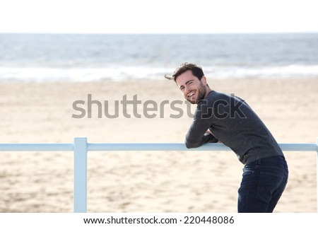 Portrait of a happy young man standing alone at the beach - stock photo