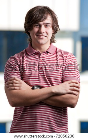 Portrait of a happy young man standing with folded hands - stock photo