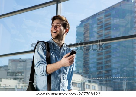 Portrait of a happy young man traveling with bag and mobile phone - stock photo